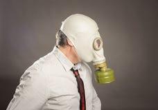 Zakenmanhand die een gasmasker dragen stock foto