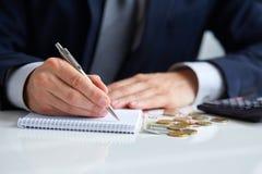 Zakenmanhand die een pen houden schrijvend op blocnote Royalty-vrije Stock Afbeeldingen