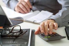 zakenmanhand die met financiën over kosten en calculator werken stock fotografie