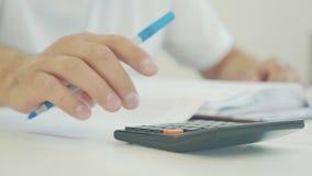 Zakenmanhand die met financiëndocumenten werken en calculator in bureau gebruiken stock footage