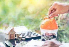 Zakenmanhand die muntstuk zetten in een spaarvarken Concept voor bezitsladder, hypotheek en onroerende goedereninvestering royalty-vrije stock afbeeldingen