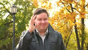 Zakenmanhand die O.K. teken, de achtergrond van de de herfststraat tonen stock video