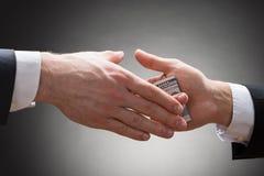 Zakenmanhand die steekpenning geven royalty-vrije stock afbeeldingen