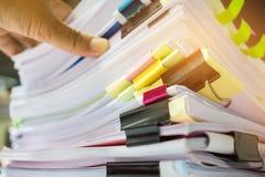 Zakenmanhanden die in Stapels document dossiers voor het zoeken werken Stock Afbeeldingen
