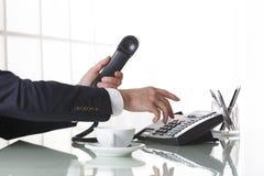 Zakenmanhanden die uit op een zwarte deskphone draaien Stock Afbeeldingen