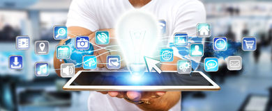 Zakenmanholding lightbulb met digitale pictogrammen Stock Foto