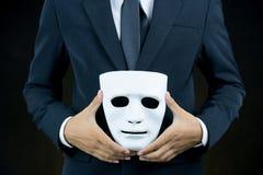 Zakenmanhuid het witte masker in de hand stock afbeelding