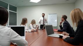 Zakenmanleider die een regeling op whiteboard verklaren aan jong commercieel team op de vergadering met in bureau stock video