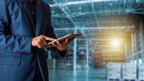 Zakenmanmanager die tabletcontrole en controle voor arbeiders met de Moderne logistiek van het Handelspakhuis gebruiken Industrie stock foto's