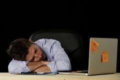 Zakenmanslaap bij het bureau van de bureaucomputer in lange werkuren wordt en wordt vermoeid verspild dat stock foto