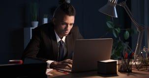 Zakenmanslaap terwijl het werken aan laptop in nachtbureau stock footage