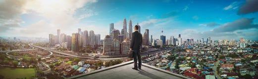 Zakenmantribune bij dak die grote cityscape mening kijken royalty-vrije stock afbeelding