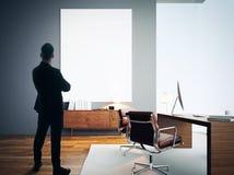 Zakenmantribunes in modern bureau met leeg wit canvas royalty-vrije stock fotografie