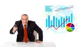 Zakenmanzitting bij bureau met statistieken stock afbeeldingen