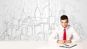 Zakenmanzitting bij de witte lijst met hand getrokken gebouwen Stock Fotografie