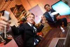 Zakenmanzitting in bureau en het werken aan Nieuwjaar` s Vooravond Hij maakt een selfie met zijn ring, die naast hem zit stock foto