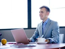 Zakenmanzitting, die achter laptop bij bureau in bureau werken stock afbeelding