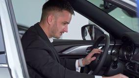 Zakenmanzitting in een nieuwe auto, die binnenland van een voertuig controleren stock video