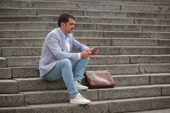 Zakenmanzitting met nieuwe draadloze tablet Mens met tablet op de stedelijke achtergrond Het concept van de elektronika De ruimte Royalty-vrije Stock Afbeeldingen
