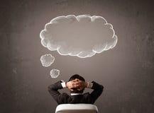 Zakenmanzitting met wolk boven zijn hoofd wordt gedacht dat Royalty-vrije Stock Afbeeldingen