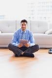 Zakenmanzitting op de vloer die tablet gebruiken die bij camera glimlachen Stock Foto