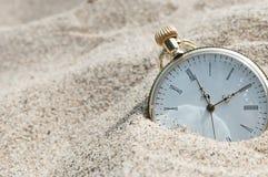 Zakhorloge in zand wordt begraven dat stock fotografie