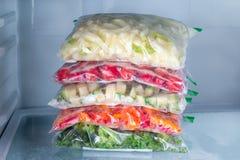 Zakken met bevroren groenten in ijskast, close-up royalty-vrije stock afbeeldingen