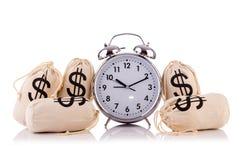 Zakken van geld en wekker Stock Afbeelding