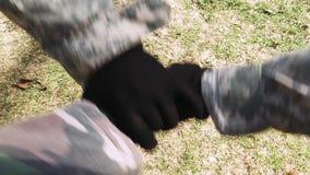Zakończenie w górę odgórnego widoku militarni ludzie stawia ich ręki wpólnie w kamuflaż rękawiczkach i kostiumach Drużynowa praca zbiory wideo