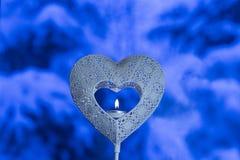 Zakończenie w górę serce kształtującego świeczka właściciela z herbaty światła paleniem w sednie z błękitnym zimy tłem z silnym b zdjęcie stock