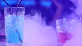 Zakończeń szkła z kolorowymi napojami i słoma na stole w dymu na tle barwione lampy zdjęcie wideo