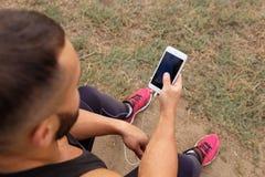 Zakończenia bodybuilder dzwoni telefon Mięśniowy mężczyzna używa technologię na zamazanym tle Styl życia aktywny pojęcie zdjęcia stock