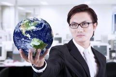 Zakończenia business manager chwyta kula ziemska przy biurem Zdjęcia Stock