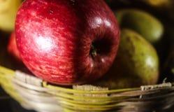 Zakończenia czerwony jabłko na koszykowym tle Obraz Stock