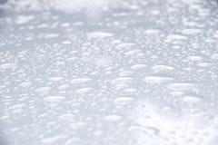 Zakończenia up kropli woda na białym podłogowym tle Zdjęcia Royalty Free
