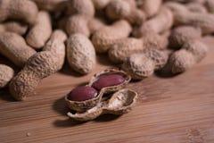 Zakończenia up/Makro- surowi unshelled arachidy na naturalnym drewnianym tle z jeden unshelled obrazy royalty free