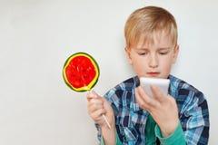 Zakończenia up profilu obrazek śliczna urocza chłopiec trzyma słodkiego cukierek w z lekkim włosy, niebieskimi oczami i zdjęcia stock