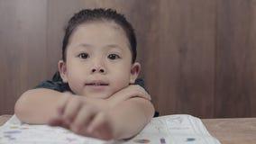 Zakończenie śliczna Azjatycka mała dziewczynka relaksuje po up zrobił jej pracie domowej zdjęcie wideo