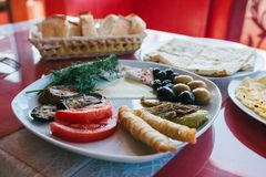 Zakończenie Śniadanie na półkowy składać się z pomidor, ser, rolka, oliwki i oberżyna, czarne i zielone Zdjęcia Royalty Free