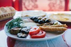 Zakończenie Śniadanie na półkowy składać się z pomidor, ser, rolka, oliwki i oberżyna, czarne i zielone Zdjęcie Royalty Free