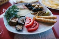 Zakończenie Śniadanie na półkowy składać się z pomidor, ser, rolka, oliwki i oberżyna, czarne i zielone Fotografia Royalty Free
