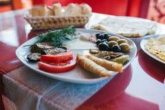 Zakończenie Śniadanie na półkowy składać się z pomidor, ser, rolka, oliwki i oberżyna, czarne i zielone Obrazy Royalty Free