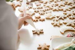 Zakończenie żeńska cukierniczka up wręcza lodowaceniu piernikowe gwiazdy zdjęcia royalty free
