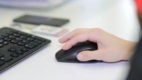 Zakończenie żeńska ręka na czarnej myszy Kobiety ` s ręka używać cordless myszy na bielu stole Zamyka w górę portreta ręki Zdjęcie Stock