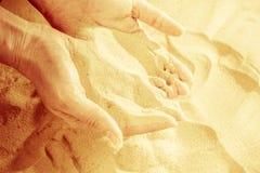 Zakończenie żeński ręki laszowanie opuszcza piasek Piaska spływanie przez ręk fotografia stock
