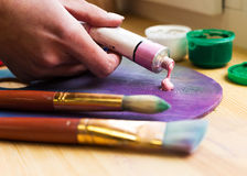 Zakończenie artist& x27; s ręka gniosąca od tubki farby na sztaludze Muśnięcia, farby, sztaluga na stole Zdjęcia Stock