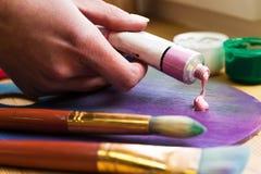 Zakończenie artist& x27; s ręka gniosąca od tubki farby na sztaludze Muśnięcia, farby, sztaluga na stole Obrazy Royalty Free