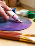 Zakończenie artist& x27; s ręka gniosąca od tubki farby na sztaludze Muśnięcia, farby, sztaluga na stole Zdjęcie Stock