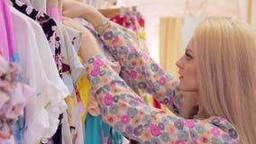 Zakończenie atrakcyjna młoda kobieta up wybiera odzieżowego na wieszaku w sklepie zdjęcie wideo