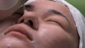 Zakończenie azjatykcia żeńska twarz na galwanicznym cleaning skóra Dziewczyna na leczniczej procedurze disincrustation w pięknie zbiory wideo